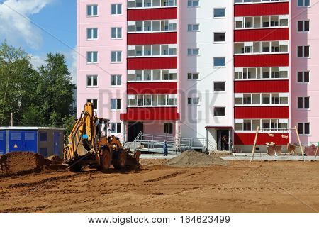 Tractor works near new building on construction site at summer sunny day