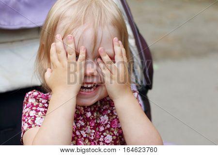 Little smiling blonde girl hides in pram outdoor closeup shallow dof