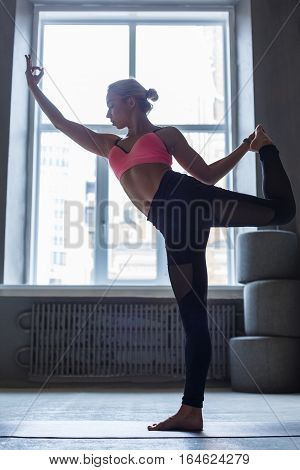 Young slim blond woman in bikram yoga class making asana exercises. Girl in backlight do standing bow pose. Healthy lifestyle in fitness club. Stretching position