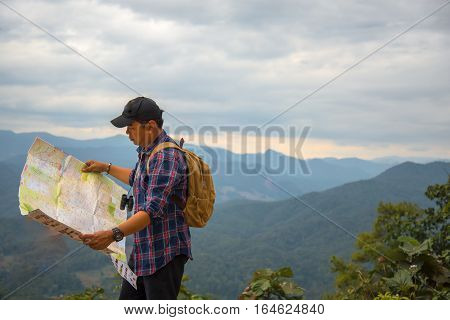 Man traveler with backpack checks map to find directions in wilderness area