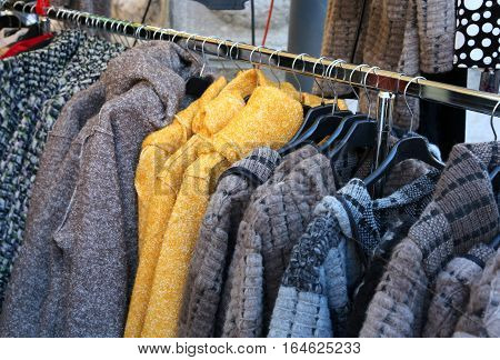 Used Clothes And Many Winter Clothes Hung On Hangers For Sale In
