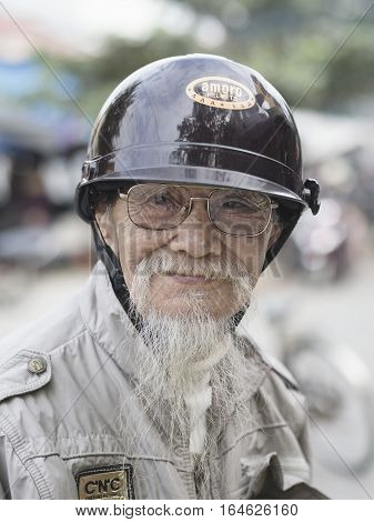Hoi An Vietnam - Dec 28 2016: Portrait of an old biker in Hoi An who keeps his goatee like his hero Ho Chi Minh.