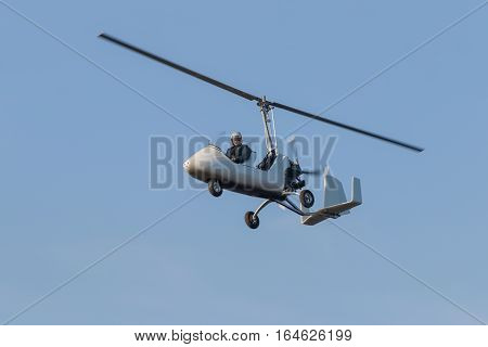 Pilot controls the helicopter out of the sky on the background of cloudless sky blue