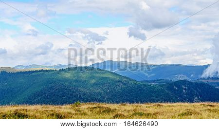 Transalpina road with hills covered with green grass Parang Mountains group in the clouds pine forests Carpathian Mountains.