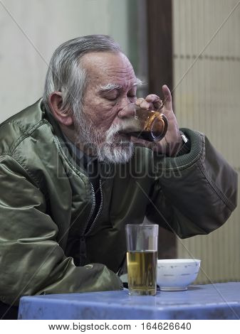 Hue Vietnam - Dec 30 2016: Old man savoring the intense pleasure of strong and dark vietnamese coffee at a cafe.