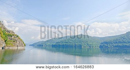 The Barrage, Dam Vidraru On The River Arges, Green Hills And Rocks, Blue Sky.