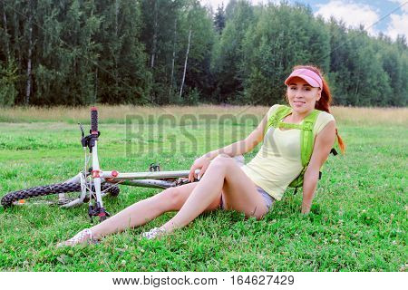 Slender girl with a backpack on his shoulders is sitting on the green grass lying next to her bike