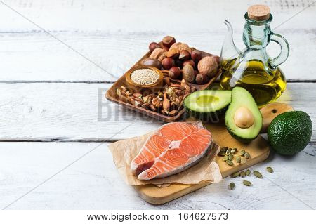 Selection of healthy fat sources food, salmon fish avocado olive oil pumpkin seeds nuts sesame on a white rustic wooden table. Copy space background