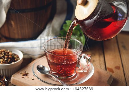Pouring hot floral tea to a glass