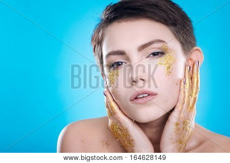 IN front of photographer. Seducing young woman touching her face and looking at you on blue background