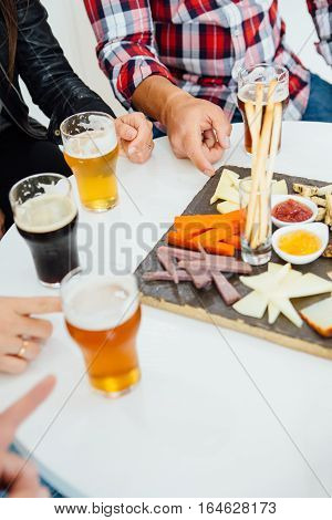 Unrecognizable people with craft beer sitting at table with various snacks