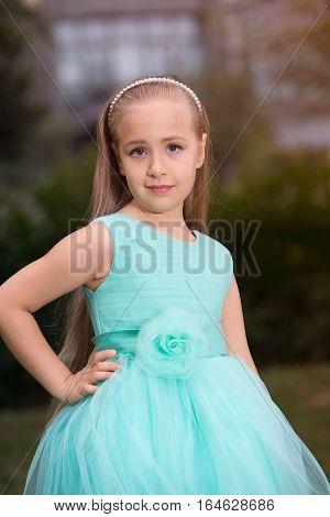Portrait of a little pretty girl un the park.