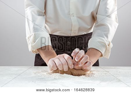 The baker making bread, male hands, kneading a dough, cooking coat