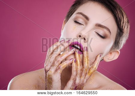 Overwhelmed with joy. Nice delighted professional model holding her hands on the face and closing eyes while posing on pink background