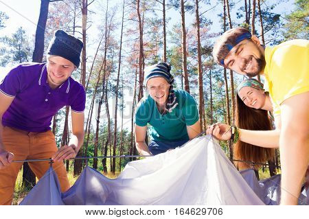Young tourists putting up a tent in the woods
