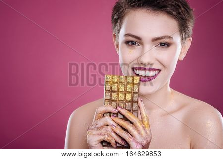 True joy. Cheerful content young woman holdign chocolate bar with tinsel and smiling while standing isolated on pink background