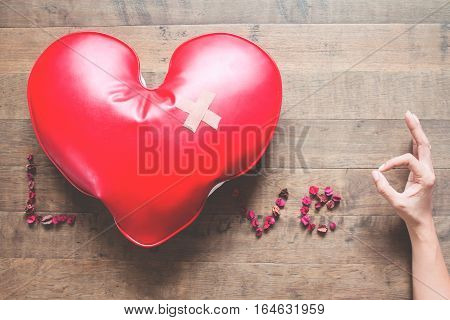 Caption word LOVE with red broken heart with bandage dried rose petals and hand sign OK. Broken heart concept on wood floor