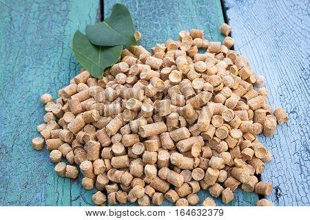 Wood pellets in the wooden background. Biofuels. Cat litter.