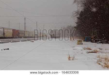 back view of a Freight train running on the railway tracks in winter while is snowing