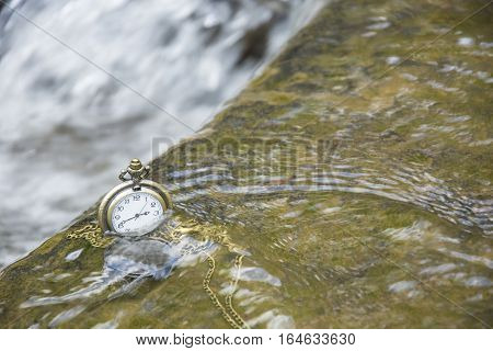 watch pocket or locket in the water fall