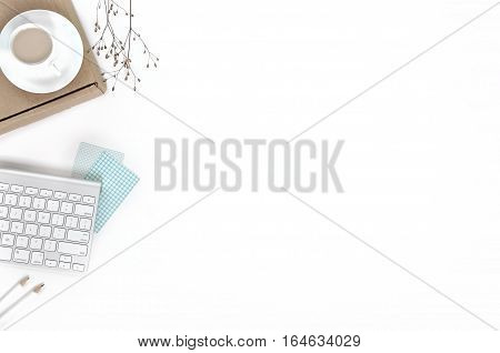 Minimal feminine workspace with keyboard, white and turquoise poster