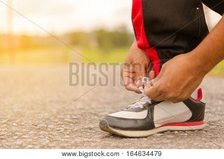 Man  tying shoes at roadside.Or sport man tying shoes.