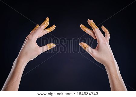 Find the position. Close up of slim hands gesturing on black background while being involved in ballet