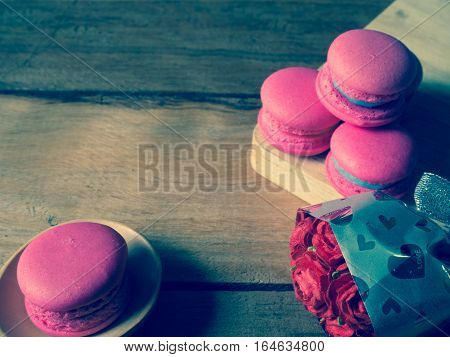 Near roses made of paper have Sweet and pink french macaroons or macarons on wooden containers. Background of dessert for St Valentine's Day. Selective and soft focus. Vintage tone.