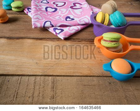 Sweet and colourful french macaroons or macarons in cup was placed on gradient orange background. Background of dessert for St Valentine's Day. Selective and soft focus. Vintage Pastel