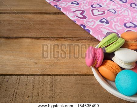 Sweet and colourful french macaroons or macarons in container ceramic white was placed on a pink heart fabric on wooden table. Background of dessert for St Valentine's Day. Selective and soft focus.