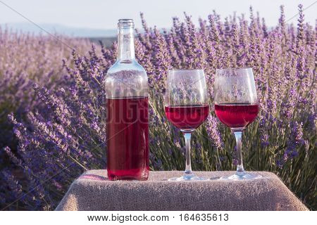 A vibrant photo of rose wine glasses and a bottle in a lavender field. The glasses are on a crate with a burlap texture, with a retro corkscrew and a cork, slightly toned
