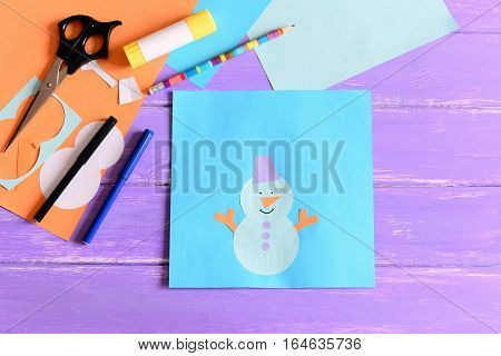 Creating a children winter paper card. Tutorial. Paper snowman card, scissors, markers, pencil, glue stick, colored paper set, snowman templates on wooden table. Children paper art on winter vacation
