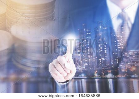 Double exposure of city and businessman standing touch the screen.