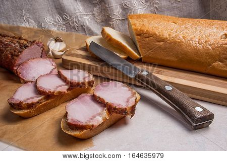 Slices Smoked Meat Or Ham And Knife On Brown Packing Paper. Tomatoes, Garlic And Small Snacks Of Bre