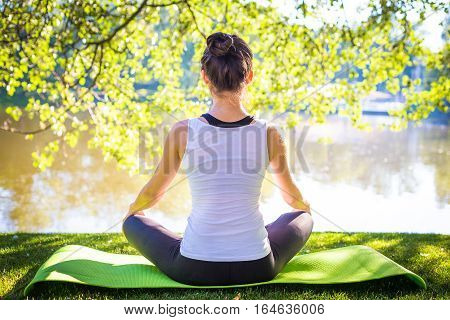 Young sport woman in white top practicing yoga in beautiful nature. Meditation in morning sunny day.