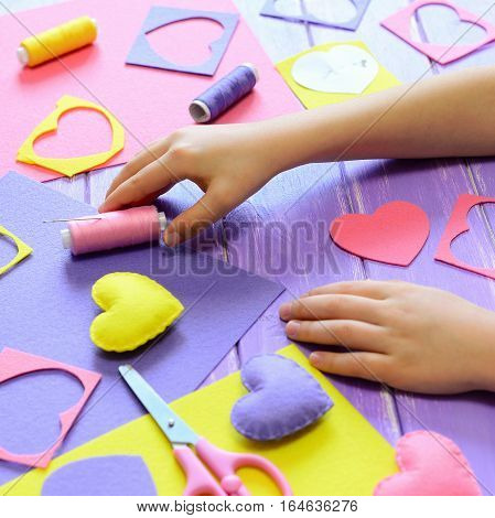 Small child made felt hearts. Children's hands on the table. Handmade Valentines day heart gifts, crafts materials and tools on a wooden table. Valentine's day or mother's day craft idea