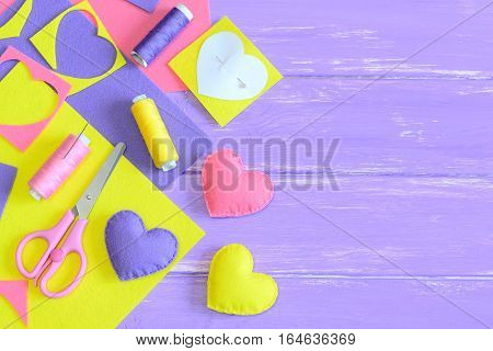 Colorful felt heart decoration set, handicraft supplies on wooden background with copy space for text. Handmade romantic gifts concept. Felt crafts for Valentine's day, mother's day or wedding