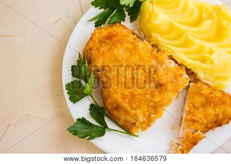 Chicken breast in breadcrumbs with mashed potatoes on a white plate