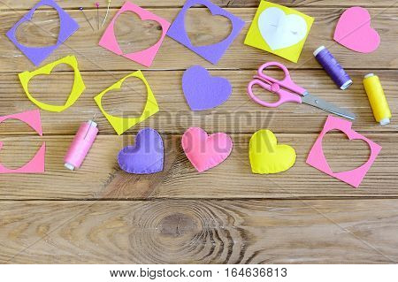 Sewing hearts crafts concept. Handmade hearts crafts for Valentine's day, mother's day or wedding. Sewing supplies on a wooden table. Basic crafts from felt. Top view
