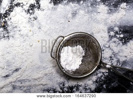 Metal strainer with spilling flour on a black background.