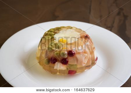 Aspic with ham and vegetables on a white plate