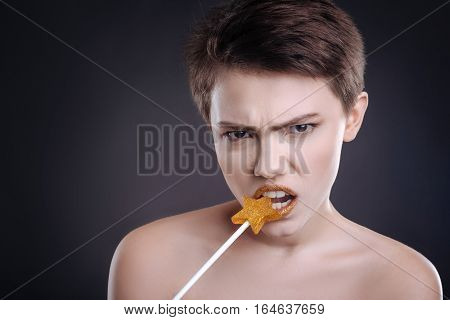 Real hunger. Pleasant emotional woman eating lollipop while posing with it against black background