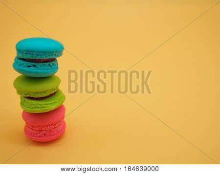 Tower Sweet and colourful french macaroons or macarons was placed on gradient orange background. Background of dessert for St Valentine's Day. Selective and soft focus. Vintage Pastel