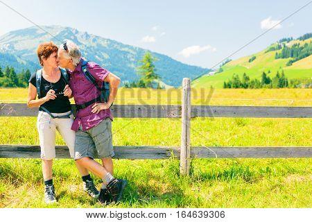 Hiking seniors taking a break next to a meadow.