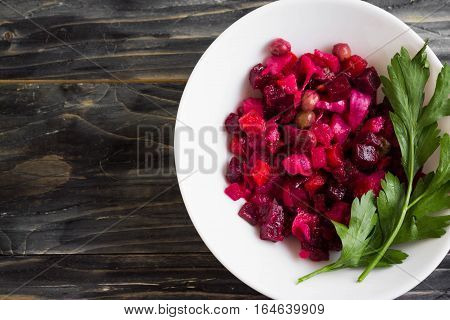 Beetroot salad in a white bowl on a wooden background in rustic style