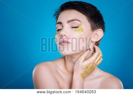 Involved in thoughts Pleasant thoughtful young woman holding her hand on th neck and closing eyes while standing isolated on blue background