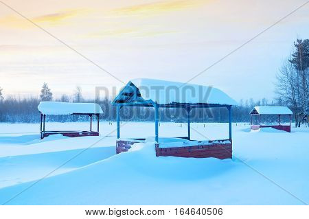 Winter morning landscape with snow-covered arbors for rest