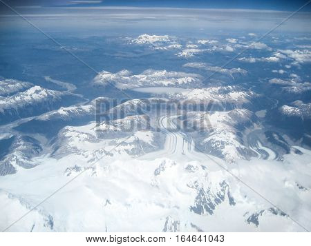Spectacular aerial view taken while flying over the peaks and glaciers of the Andes mountain range in South America.