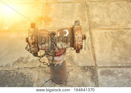 The rusty old metal water pipe at public under the sunlight and on street