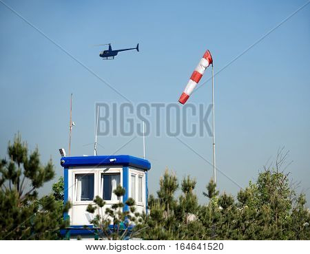 Small blue helicopter flies over an airfield weather station in summer cloudless day